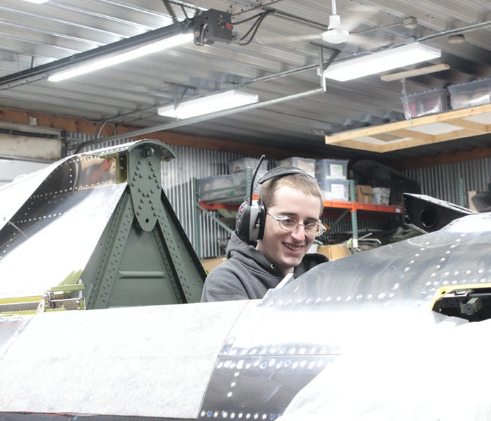 Aaron works at system installation in the P-47 cockpit.