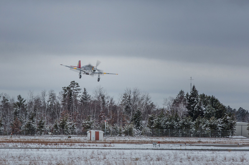 The Red Tail lands after a successful test flight with a background of snow.