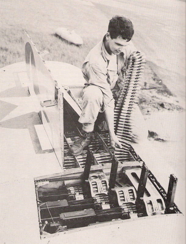 Crewman loading .50 caliber rounds into the ammunition chutes on a P-47, USAAF photo