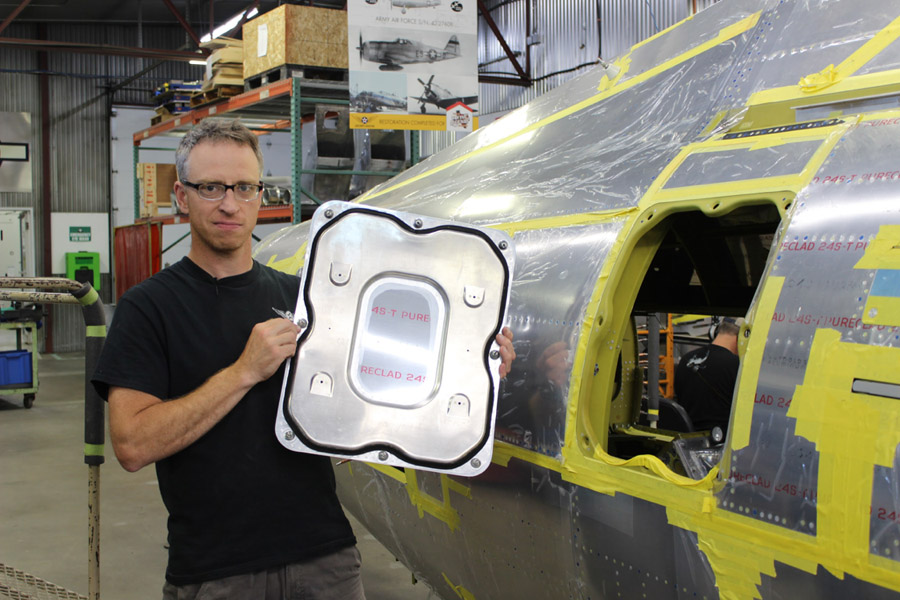 Restoration manager Ryan Underwood holds the main access door of the P-47 before we shipped it to Major General Searles.