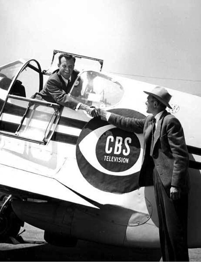 Joe DeBona(cockpit) shakes hands with Jimmy Stewart in a publicity shot showing the CBS logo.