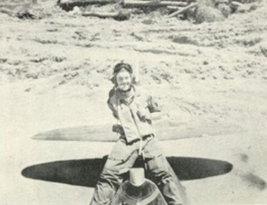 Lt. Searles sits astride the rear fuselage of Little Chum.